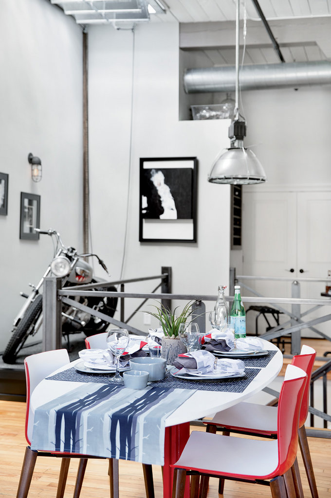 The modern dining table, from the Habitat for Humanity ReStore, is backed by an old gymnasium light Hodge restored. A 1964 Triumph motorcycle draws attention from the corner.