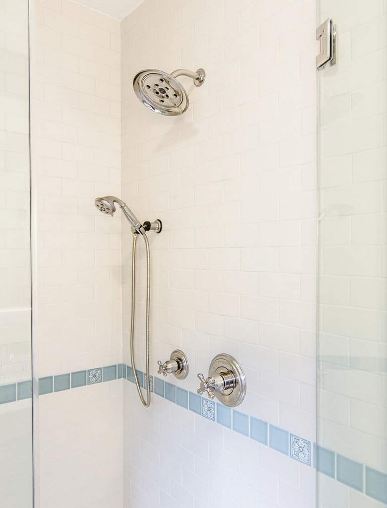 Subway tiles in a matte linen finish, light blue paint, and a glass shower door lend a sense of spaciousness.