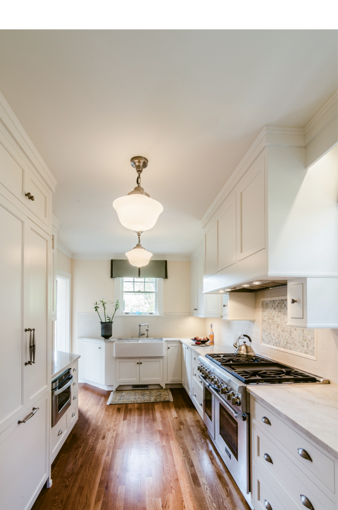 At Doug and Wendy Banks' 1925 North Asheville home, a breakfast nook was sacrificed to create a spacious galley kitchen. Warm white Shaker cabinets,  antique pewter hardware, and ecole-style pendant lights lend classic appeal while still feeling new.