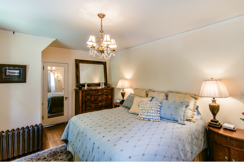 In the master bedroom, one of the windows had been obscured with shelves. The renovation involved restoring the windows, repairing and painting the stucco walls, and refurbishing all the light fixtures.