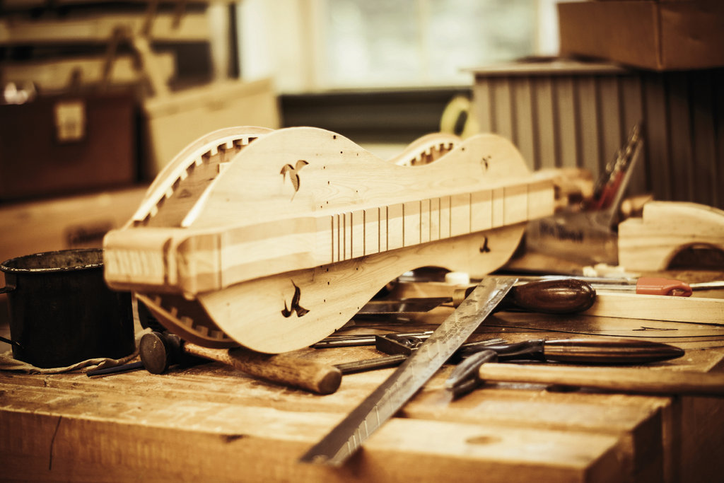 In the woodworking studio, a half-complete dulcimer sits on a workbench. The instrument will be finished by the end of the week.