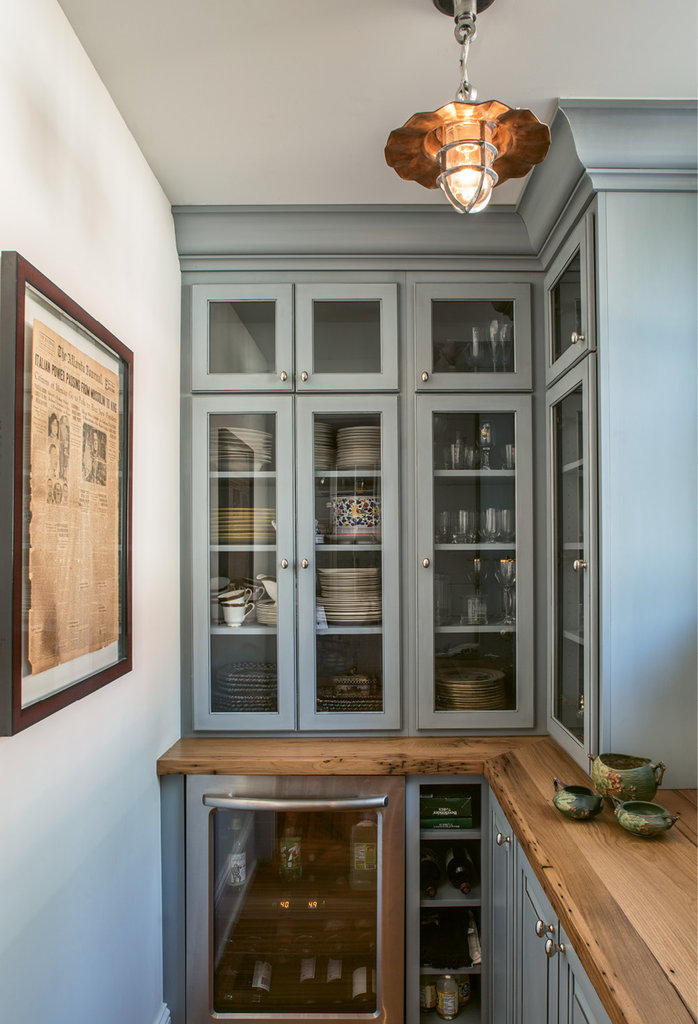 A small pantry holds servingware, while framed on the wall is a little piece of the house: a newspaper from 1929 that was found in the wall during renovations.