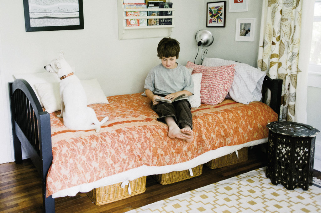 Noah enjoys a book with Luna in his bedroom, where a mix of colors and patterns makes for a lively space.