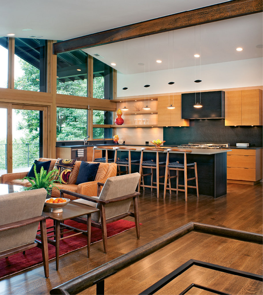 The configuration of the second floor changed to allow for an open kitchen, living, and dining area. New floor-to-ceiling windows brighten the modern space, and great care was taken to manage the transitions between materials.