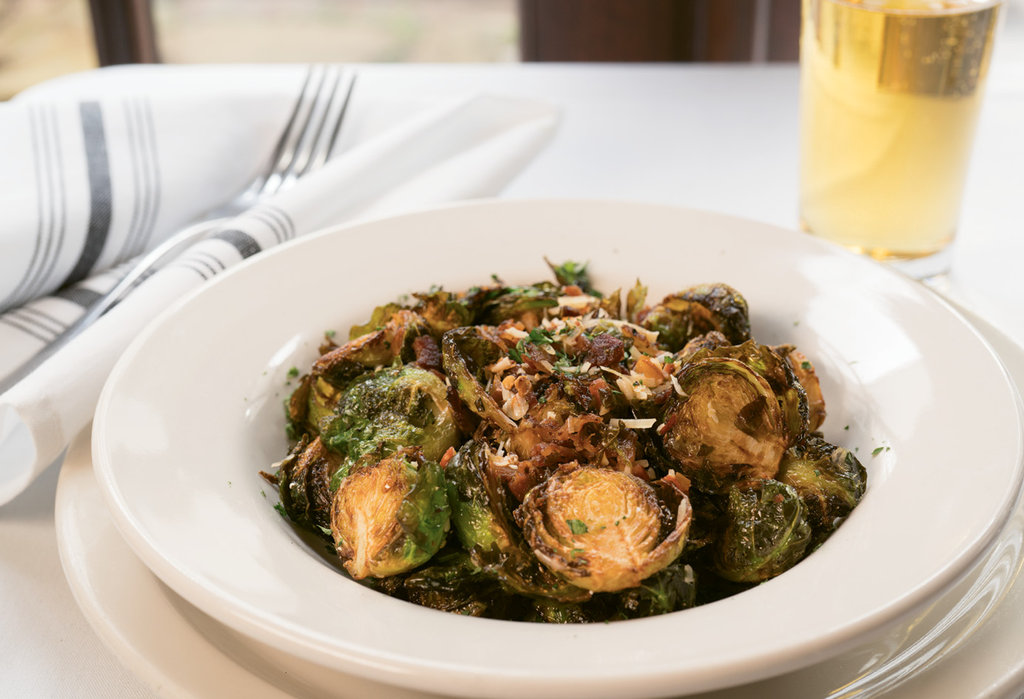 Southern Comfort Crispy Brussels sprouts are savory with bits of maple-peppered bacon, Parmesan cheese, and pickled cherry peppers.