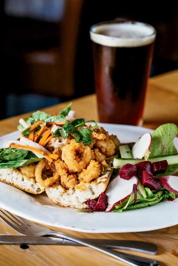 Calamari bánh mì, with arugula, herbs, pickles, and charred lemon mayo, represents his use of global flavors.