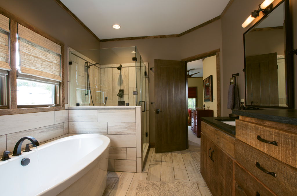 In the master bathroom, long, light color tiles lengthen and brighten the floors, half wall, and shower. A soaking tub replaced an outdated Jacuzzi, and a new vanity was constructed at the WSM Craft Shop from the best specimens of reclaimed wood.