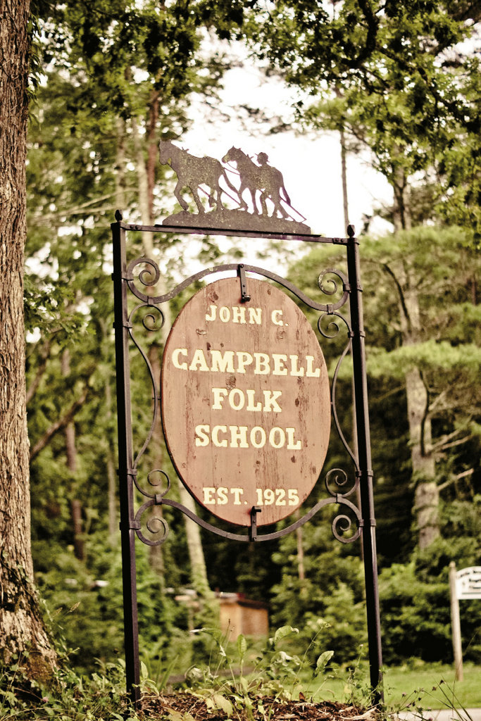 """Metalwork at the front gate depicts the oft-cited campus motto, """"I Sing Behind the Plow."""""""