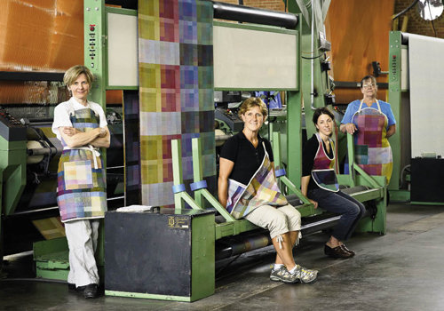 Artistic  Director Bethanne Knudson, Director of Education Kelly Hopkin,  Western Carolina Sewing Company owner Libby O'Bryan, and  Bonham wear aprons made at the mill in Hendersonville.