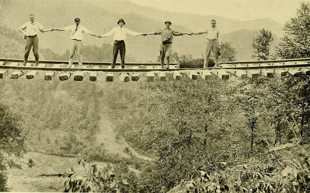 Railway workers braved a portion of track between Old Fort and Ridgecrest, where the earthen support had been completely washed out.