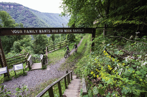 Adam Stephens and Justine Jenkins with Marathon Bicycles hit the track at the Arrowhead Trails, a 13-mile network of mountain biking paths along the edge of the gorge. Above, the Kaymoor Trail passes a historic coal mine site that once warned workers to take precaution.