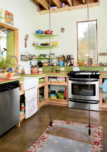 Bright Ideas Before building, Cummings kept a notebook of decorating ideas. The swing in the kitchen (above) was inspired by one a friend had in her home. Right, a window in Olive's nook offers a bird's eye view of the kitchen. Opposite, a whimsical hot air balloon mobile and paper lanterns hang in a window.