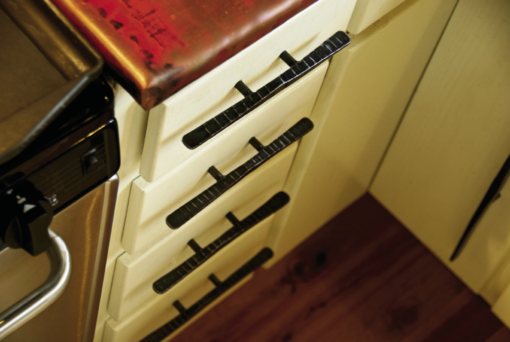 Drawer pulls, forged by Dean, complement the copper countertop.