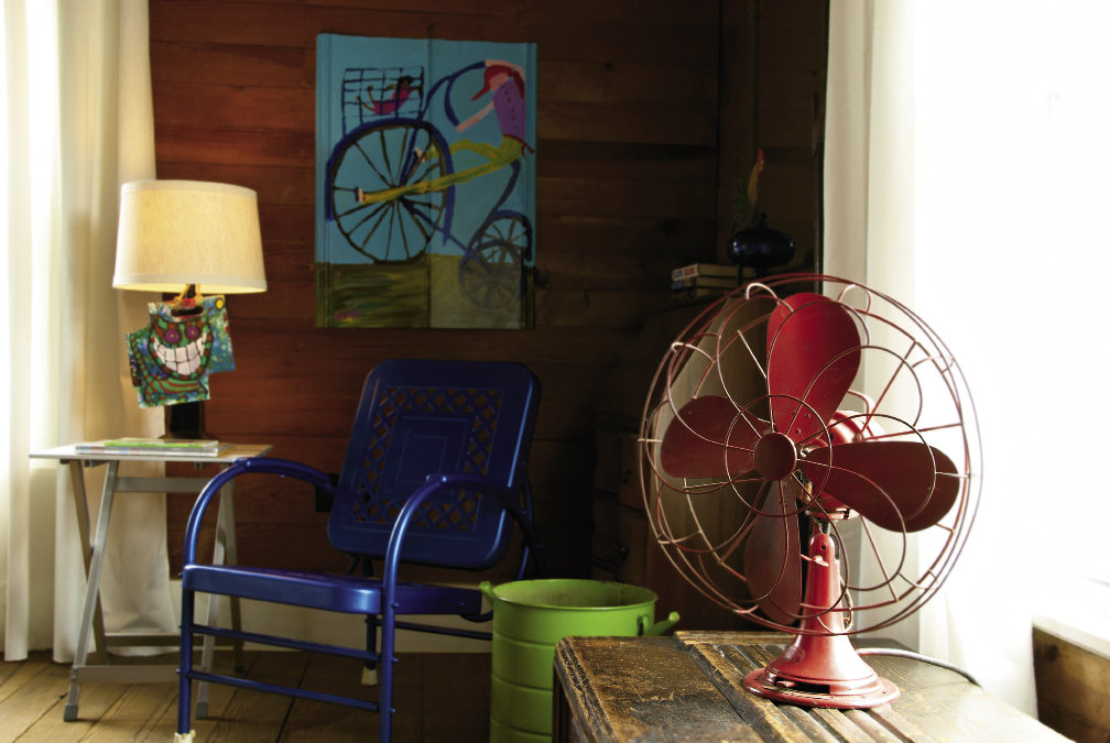 The bright red of a vintage fan and blue of a metal chair infuse a guest room with color.
