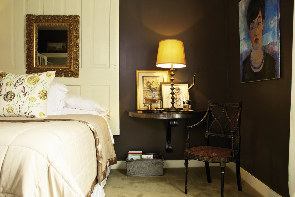 the  master bedroom's half-moon bedside tables crafted by Dean and an eclectic selection of paintings and drawings give the space an artistic touch.