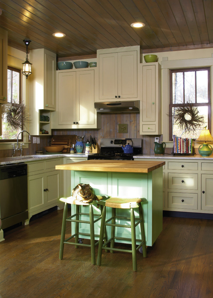 Oscar lounges on a stool in the kitchen, which incorporates design elements of the 1920s and '40s. Pops of green jump from the island, cabinet knobs, and pottery.