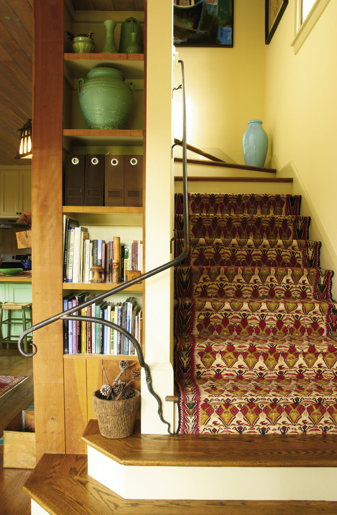 Niches throughout the compact, three-story home hold guidebooks, collected finds, and art. Dan Howachyn of Black Mountain Iron Works forged the handrail. The stair runner is from Wisteria.