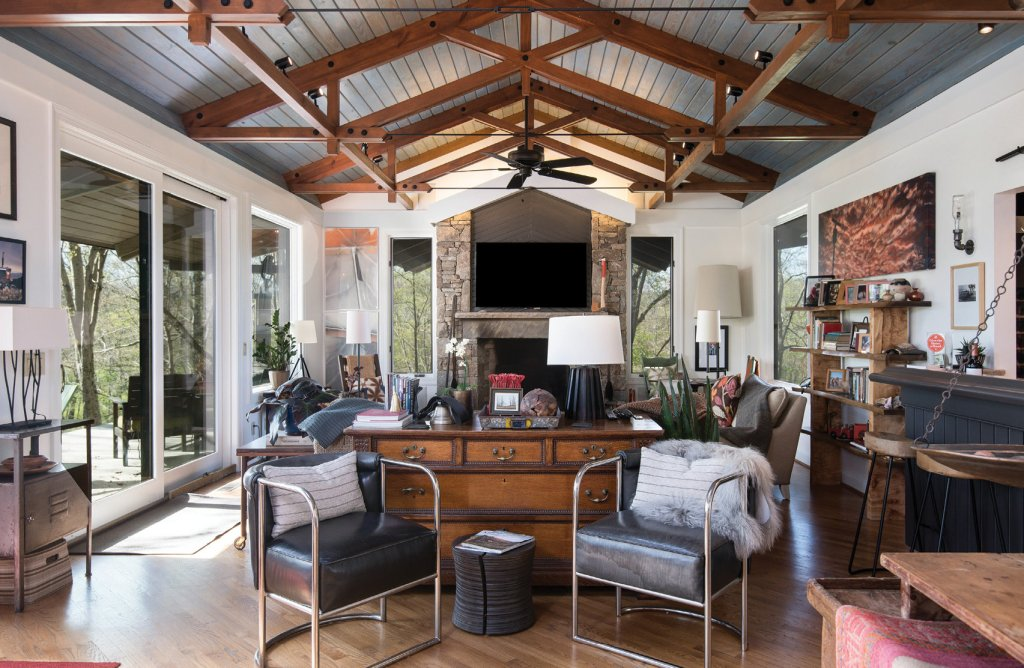 In the living room and den, Platt painted everything white, updated the lighting with modern fixtures, added track lighting, and removed the curtains. His taste in eclectic art and furnishings enhances the look.