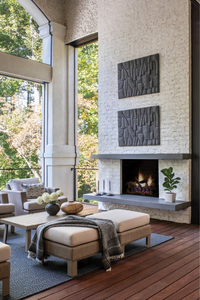 Accessed via folding doors from the living and kitchen area, the outdoor living room is an oasis overlooking the pool and back patio. The fireplace received an overhaul; stone was replaced with white-painted bricks and new cement mantles.