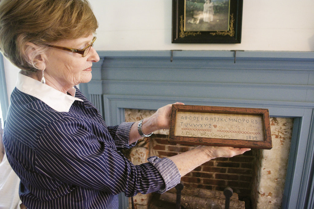 Executive  Director Linda Cloherty holds a piece of  embroidery done by a young slave in 1832.