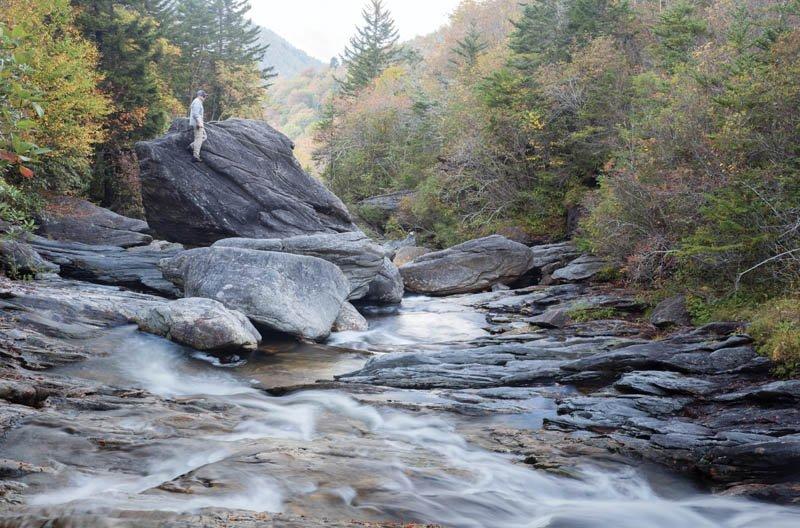 Point of View - In the headwaters of the Pigeon River, an angler ascends boulders to get a vantage point for locating skittish trout.