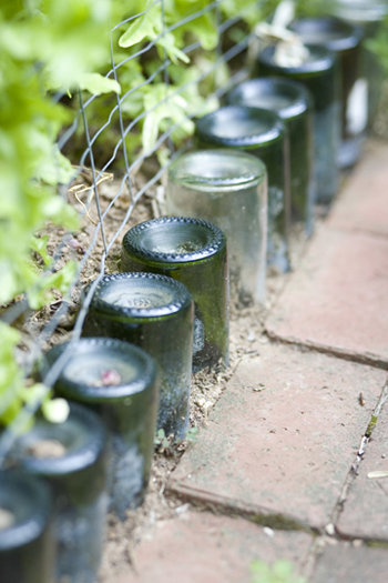 Wine bottles add interest to a garden border.