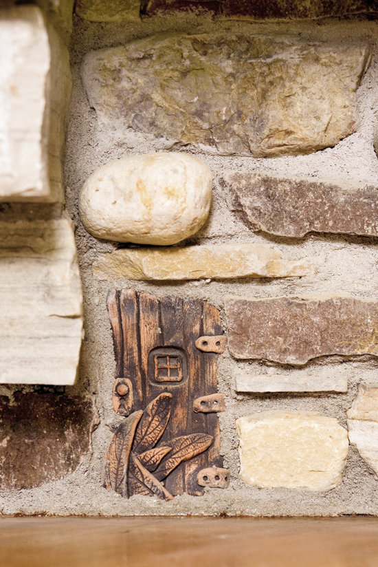 """The rock fireplace holds a touch of whimsy—a """"fairy door"""" hidden in the stonework."""
