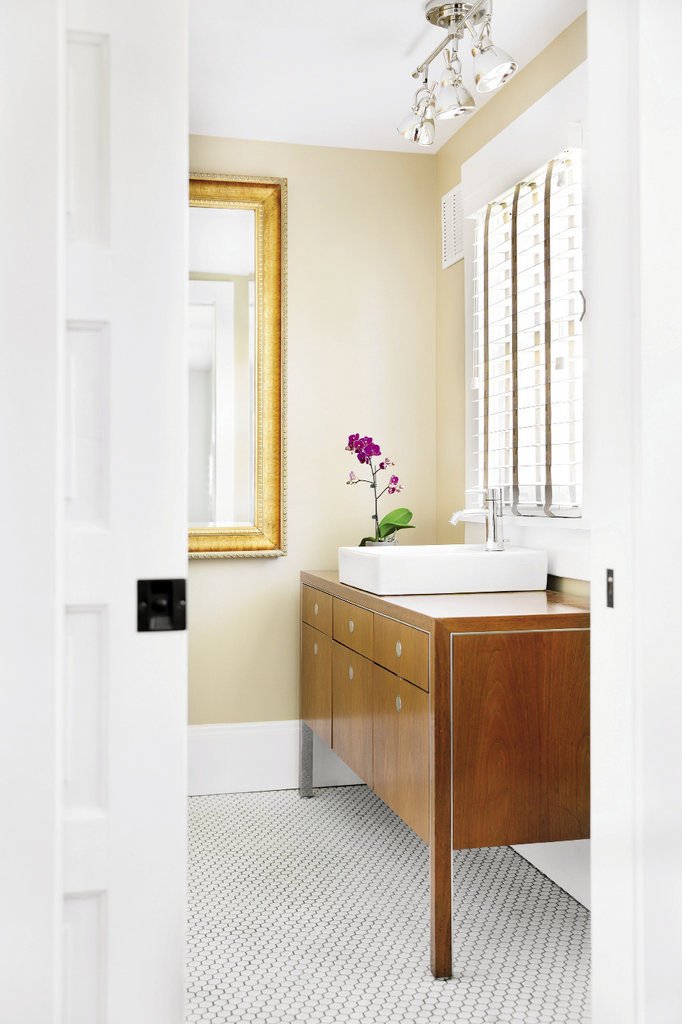The bathroom, which holds a mid-century Ward Bennett sideboard-turned-sink, connects to the bedroom via a small office space and walk-through closet.