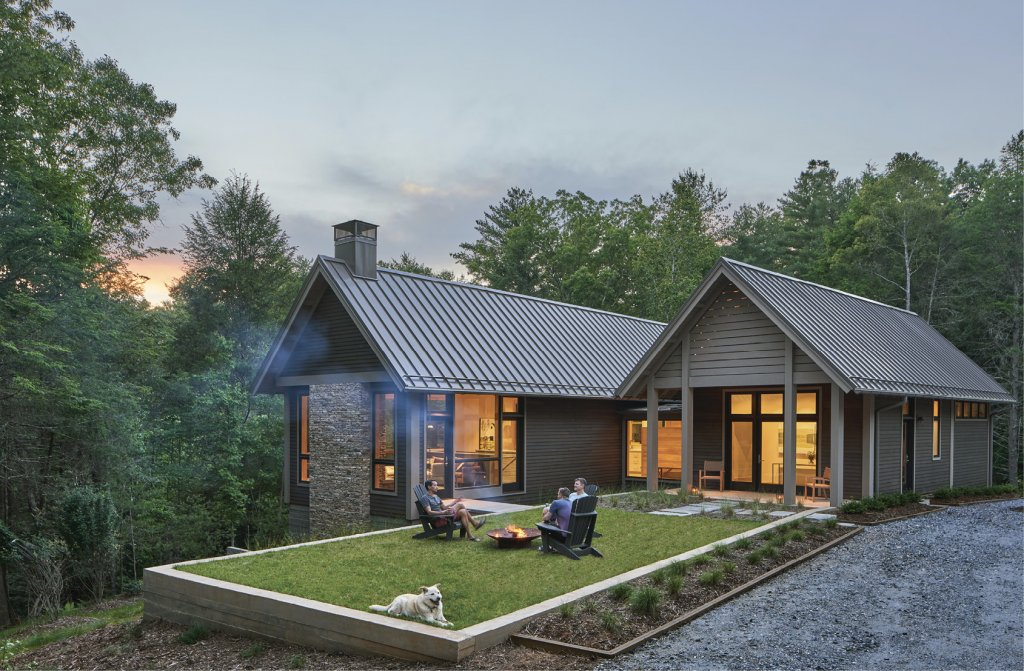 Outdoor Hang - With stained cedar siding and vanilla-hued stone, the home's dusky façade blends into the surrounding forest. A small lawn with a fire pit is accessible from the master suite and from the living room via a small bridge, which spans a narrow creek bed separating the two sections of the home.