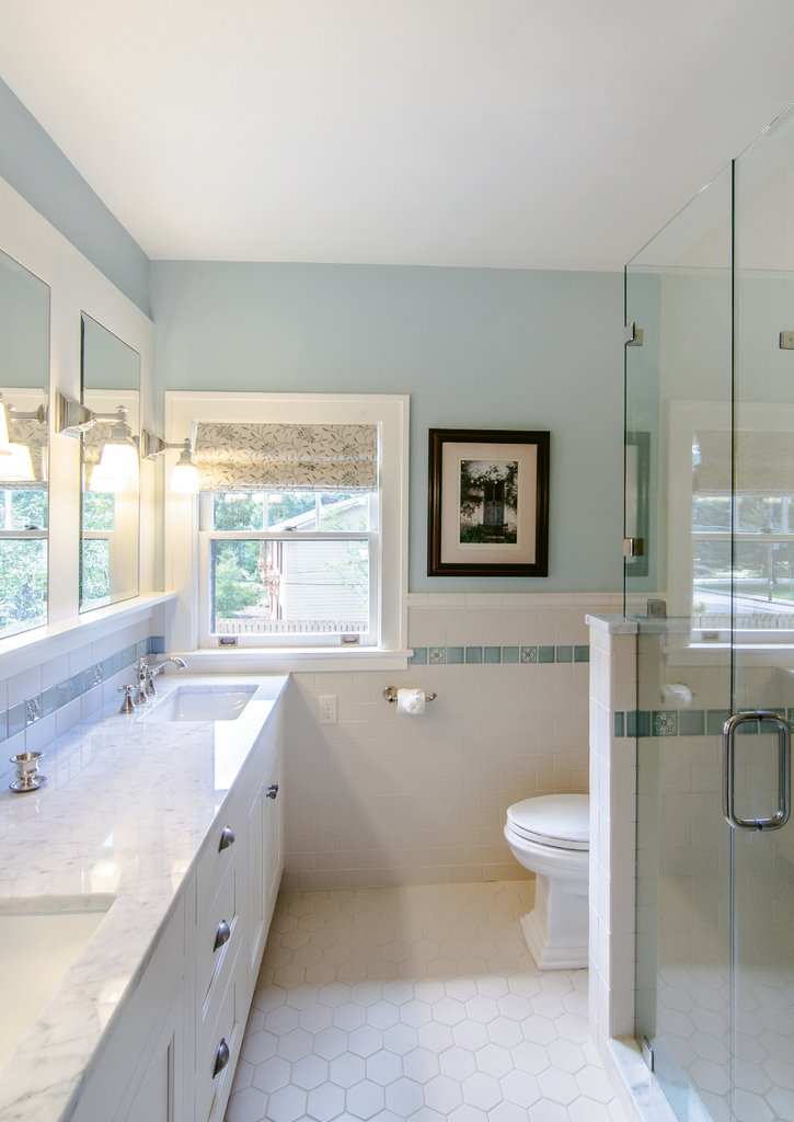 The main bathroom was taken down to the studs to allow for a new shower, toilet, and dual sink vanity. Inset framed mirrors, one of which was original, conceal cabinets.