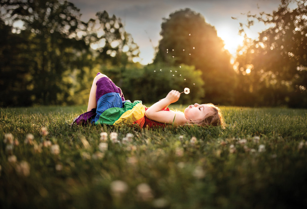 1st PLACE PROFESSIONAL CATEGORY - Wishing Flower - Valerie Eidson - Taken at a golden hour at her family's home in Fairview, Eidson snapped this pic of her daughter blowing on a dandelion, whose fuzz is perfectly illuminated in the soft light.