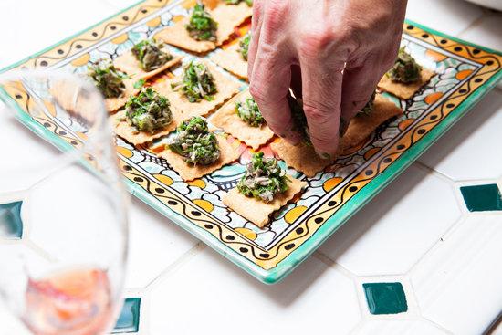 An appetizer of black snake salad on crackers.