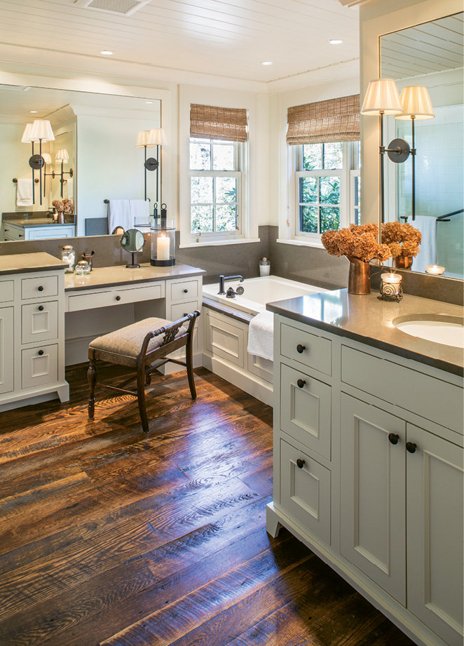 The master bath doesn't miss a beat, featuring a tub, shower, two sinks, a vanity, and lake views.