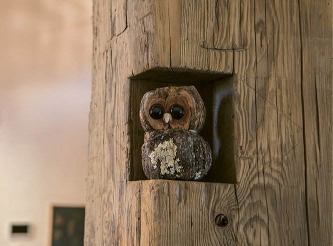 A wooden owl sits in a notch of a timber-frame beam. Right, a half-bath sink was built from a stump and a rock found by the family.
