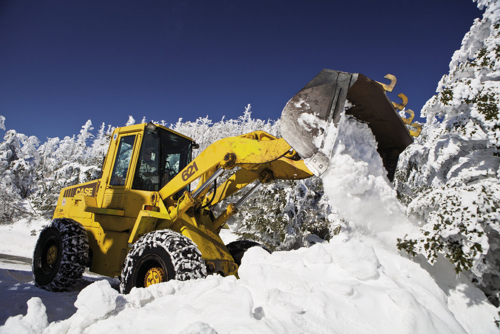 The park's front-end loader takes a bite out of winter on its way to clearing the summit road.