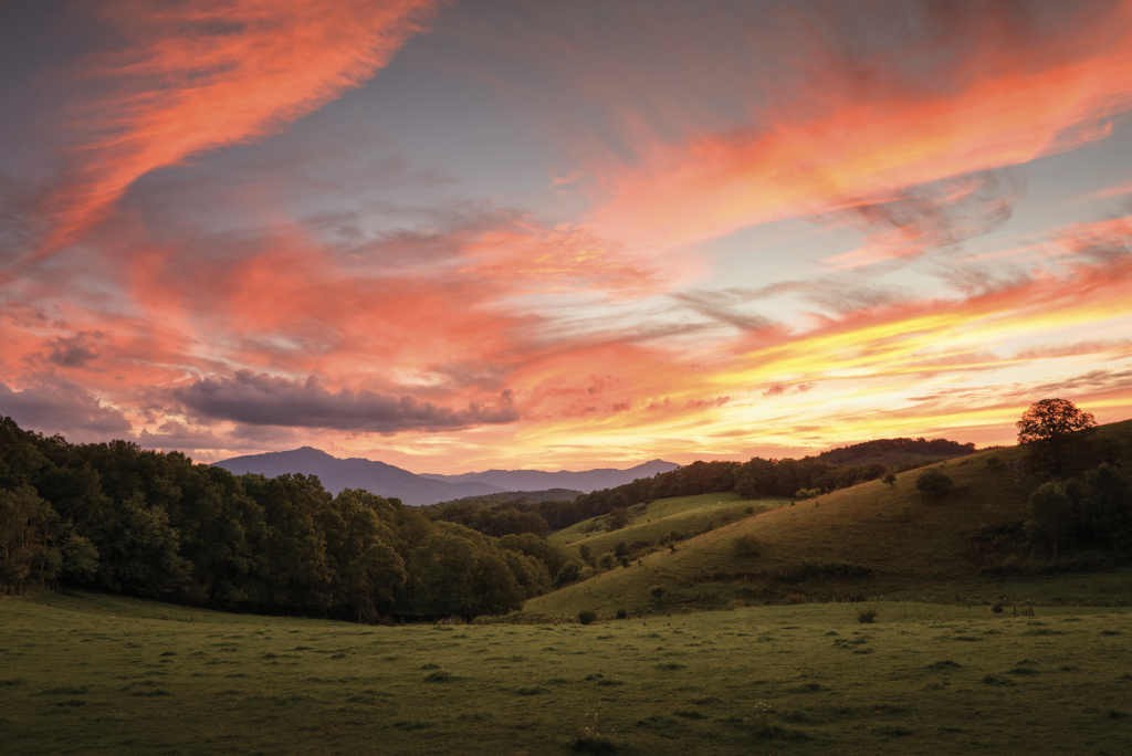 Blazing Sky - Green pastures and blue ridges set against a brilliant sunset at Moses Cone Memorial Park