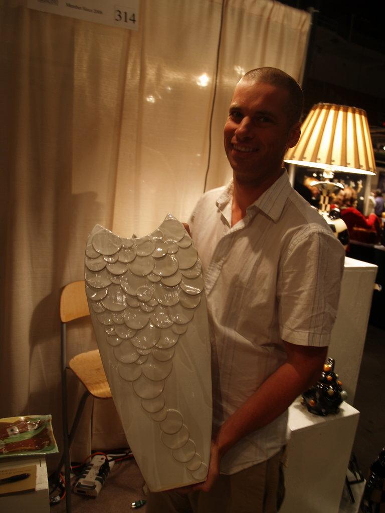 Asheville ceramicist Sandy Batton holding a kiln-fresh vase.