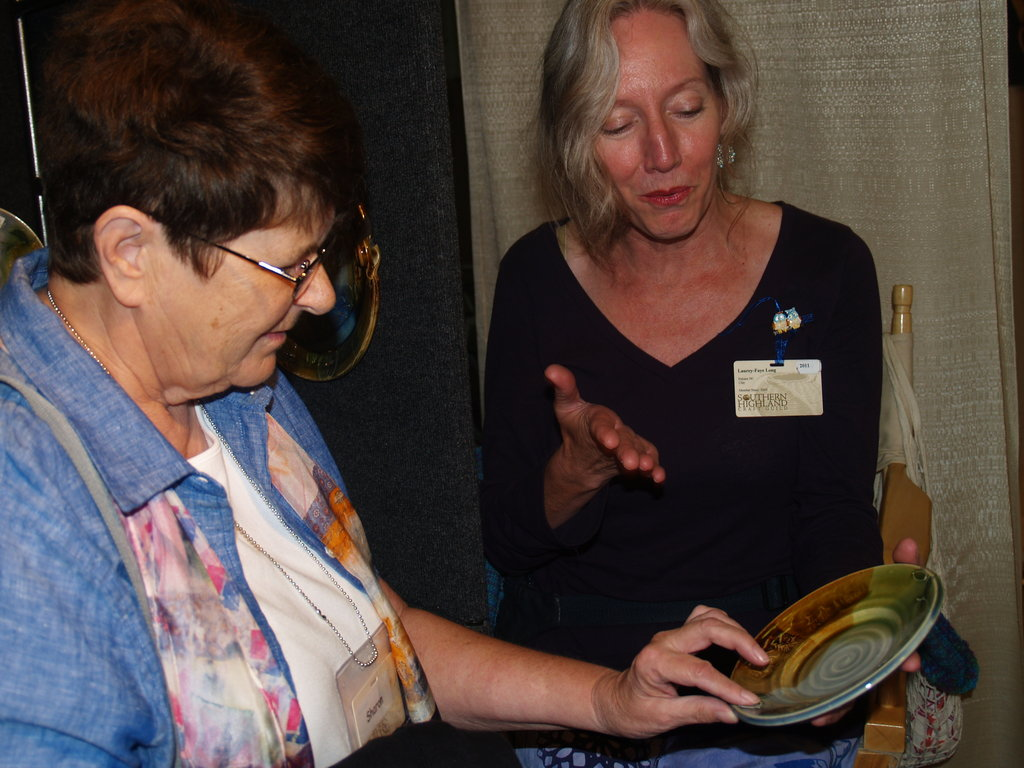 Cat Jarosz explains her ceramic process to an eager collector