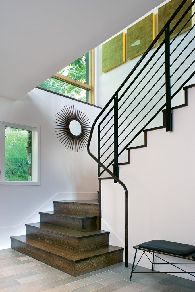 Expansive upper level windows allow light to flood the relocated stairwell. A wooden handrail is a graceful touch.