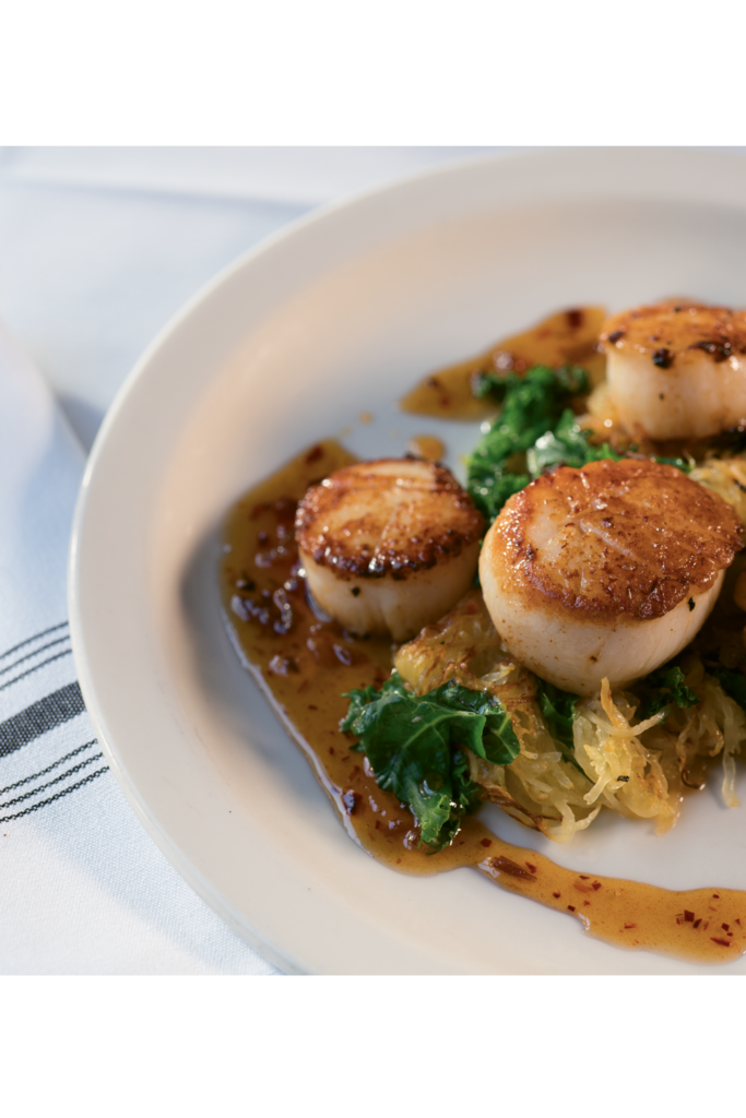 Sweet & Savory - Pan-fried sea scallops with spaghetti squash, kale, and a bacon-date gastrique from Star Diner in Marshall