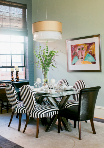 The dining area is vibrant with striped chairs by Mitchell Gold + Bob Williams and a modern glass-top table. Cher Shaffer's piece, Mountain Fairy, brings color and whimsy to the space.