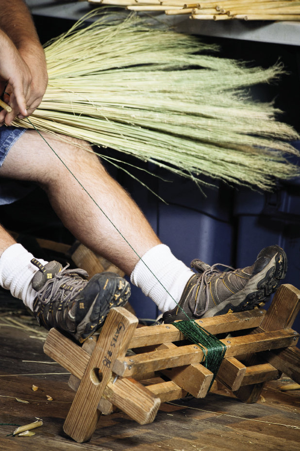 Using a foot wheel, a wooden bobbin loaded with twine, Marlow binds the broomcorn one stalk at a time around the handle