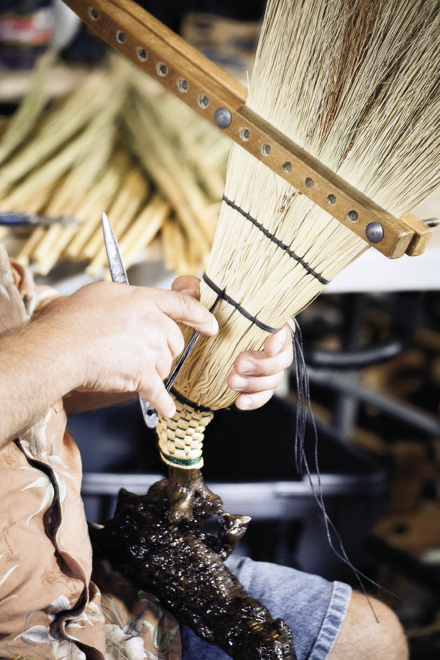 a wooden spreader clamps the broom while Marlow hand-stitches the twine that holds the brush flat.