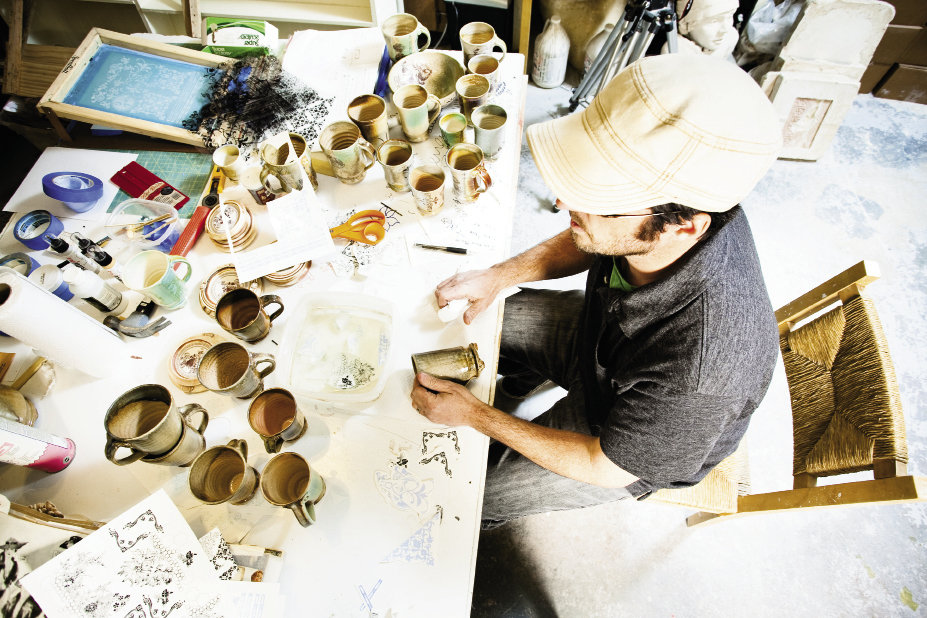 Phillips soaks decals in water solution before affixing them to his glazed pottery for a final firing.