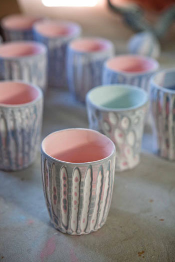Glazed, textured cups await their turn in the kiln.