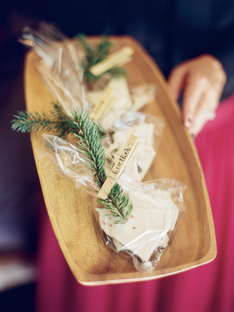 Party favors, such as homemade peppermint bark packaged and adorned with evergreen sprigs and guests' names, are a thoughtful way to say thanks for coming.