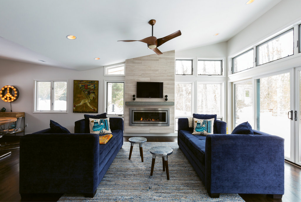 An eight-foot ceiling and minimal windows made the dining and living room feel like a cave. Adding a pitched butterfly roof and windows made a world of  difference. The fireplace received a modern face-lift as well.