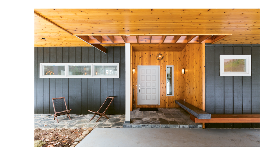 The new roof was  integrated with the porte cochere, and a cut-out above the entry presents light and inviting appeal. The original siding was painted dark green, while the orange-toned knotty cedar soffit and doorway lend warmth.