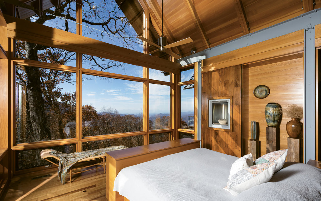 Natural Sanctuary - The master suite is comprised of the bedroom, with floor-to-ceiling windows, ample closet space, and a beautiful bathroom with his and her sinks, a tile shower, dry sauna, and window-facing soaking tub.  The sounds of rain and acorns plodding on the metal roof, the cross-breezes drifting through the open windows—the sights and sounds of the home make living here a sensory experience.