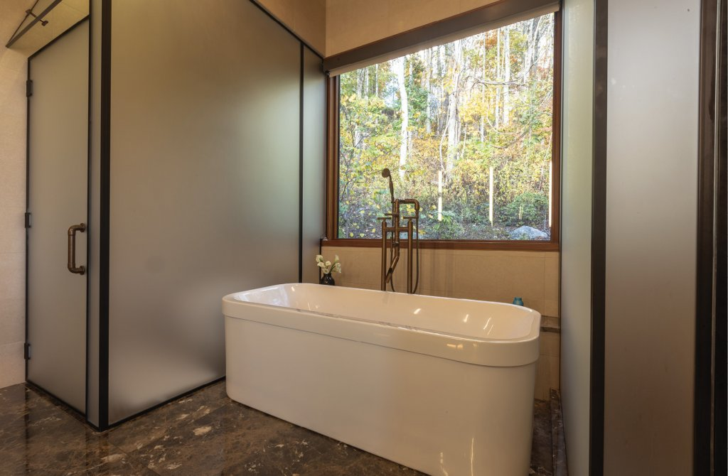 In the master bath, frosted glass encloses the toilet and shower, while the tub is positioned for a private view of nature.